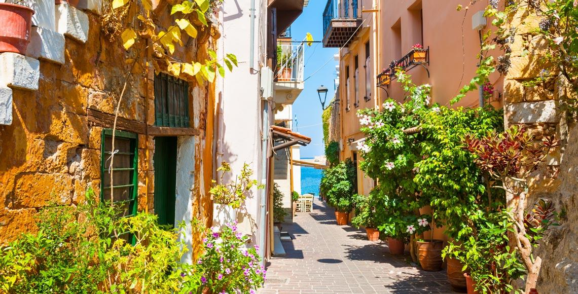 calles llenas de plantas y colores con el mar al fondo en el casco antiguo de Chania