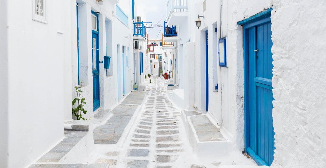 Calle de casas blancas y puertas azules en Mykonos
